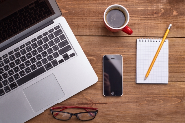 macbookとスマホとコーヒーの画像