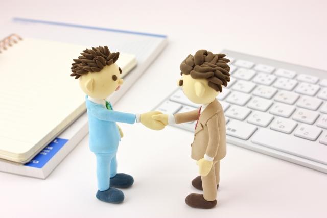 ビジネスマンが握手する人形画像