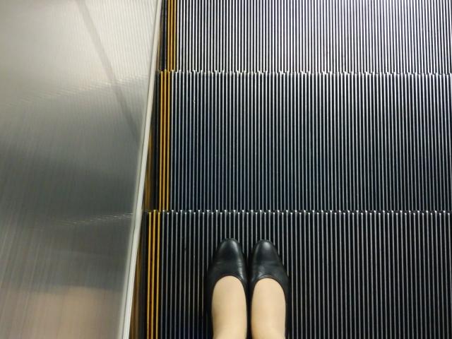 エスカレーターの左側に立つ女性の足 画像