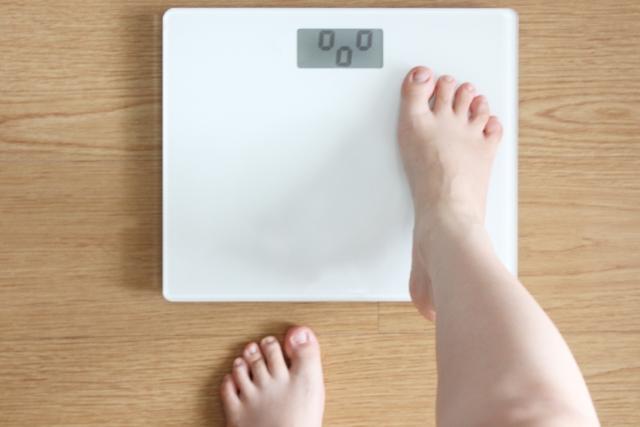 体重計に乗る足を写した画像