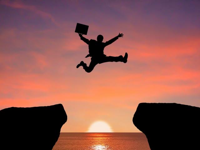 崖を飛び越えるサラリーマン 画像