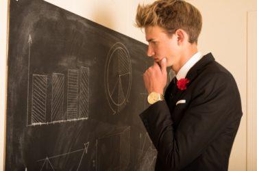 黒板を見ながら考える男性 画像